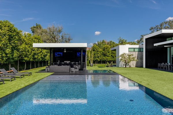The backyard features an artificial lawn and a pool that comes right up to the grass' edge. Photo 11 of Ponce Davis Residence modern home