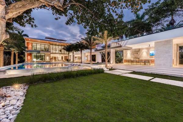 Modern home with outdoor, back yard, trees, grass, large pool, infinity pool, shrubs, walkways, large patio, porch, deck, stone patio, porch, deck, and landscape lighting. The rear of the home as seen from the water. Photo  of Palm Island Residence
