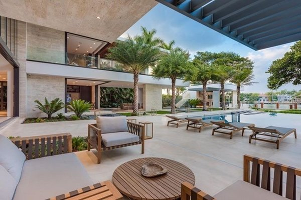 Modern home with outdoor, back yard, trees, stone patio, porch, deck, and large patio, porch, deck. The main outdoor patio has plenty of shade provided by the large overhangs. Photo 3 of Palm Island Residence