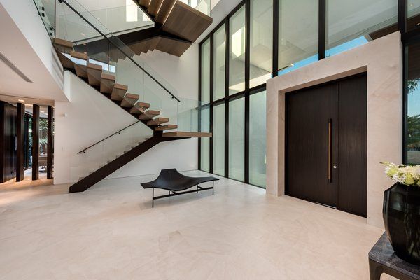 Modern home with staircase, wood tread, and glass railing. The statuesque staircase made of metal, wood and glass sits just off the main entrance. Photo 6 of Palm Island Residence