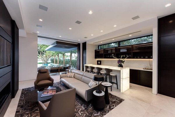 Modern home with living room, sofa, chair, recessed lighting, limestone floor, and ribbon fireplace. A bar and lounge is found secluded on the right side of the home with access to the backyard and views of the water. Photo 8 of Palm Island Residence