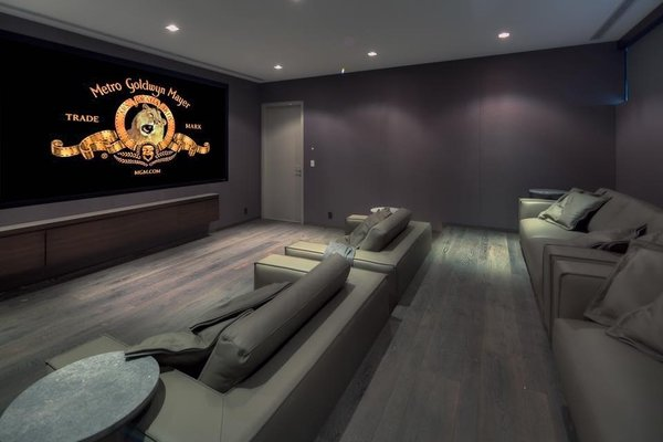Modern home with living room, sofa, medium hardwood floor, and recessed lighting. The home's modern theater room offers stadium-style seating with leather couches and wood flooring. Photo 9 of Palm Island Residence