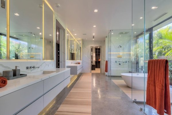 Modern home with bath room, freestanding tub, wall mount sink, marble wall, enclosed shower, recessed lighting, track lighting, and marble counter. The master bathroom features separate his and hers vanities and showers. Photo 11 of Palm Island Residence