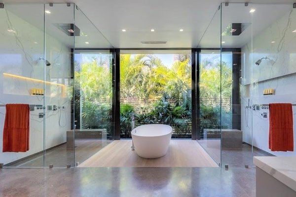 Modern home with bath room, recessed lighting, enclosed shower, freestanding tub, and marble wall. A stand-alone tub sits between the two glass-enclosed showers. Photo 12 of Palm Island Residence
