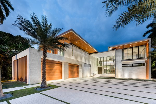 Modern home with outdoor, front yard, large patio, porch, deck, trees, stone patio, porch, deck, pavers patio, porch, deck, and landscape lighting. Tropical elements such as Ipe wood, stone, glass, and water features are found throughout the exterior of the home. Photo 13 of Palm Island Residence
