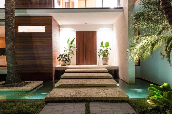 Modern home with wood, swing door type, exterior, outdoor, front yard, trees, raised planters, small pool, stone patio, porch, deck, and landscape lighting. Large limestone steps take you over a reflecting pond toward the front door. Photo 2 of Casa Ischia