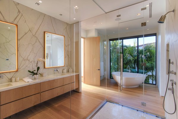 Modern home with bath room, marble counter, light hardwood floor, wall mount sink, freestanding tub, enclosed shower, recessed lighting, and marble wall. The master bath features dual vanities, a stand-alone tub, and a glass-enclosed shower. Photo 7 of Casa Ischia