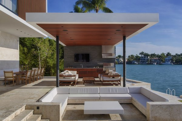 Modern home with sectional, recessed lighting, limestone floor, back yard, stone patio, porch, deck, kitchen, wood cabinet, stone tile backsplashe, drop in sink, range hood, and range. A conversation pit located by the pool brings a touch of mid-century to this modern oasis. Photo 8 of Casa Ischia