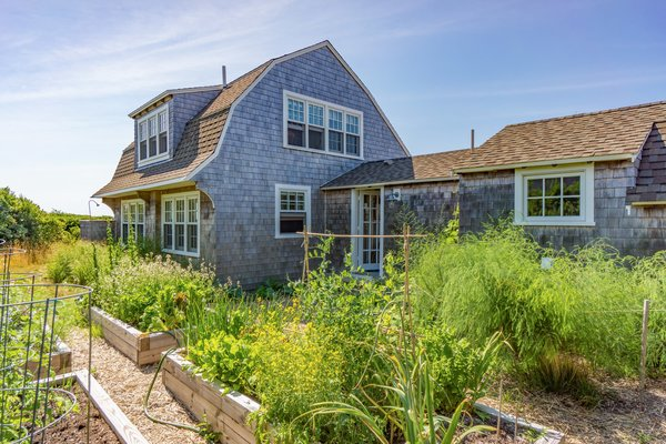 On the sunny south side of the existing rehabilitated 1880 structure, repurposed as a summer guesthouse, is a florishing garden which provides the owners with fresh vegetables, raspberries and blueberries. Photo  of Corkin House modern home