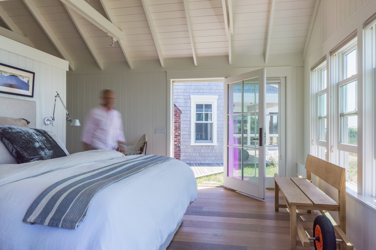 A modest bedroom sits functionally askew to the main part of the cottage to provide a panoramic view of Provincetown harbor - a spectacular view of twinkling nighttime shore lighting as the dunes curve toward the tip of Cape Cod. The open french door leads to a secluded hot tub and deck area.  Corkin House by KRUEGER ASSOCIATES ARCHITECTS