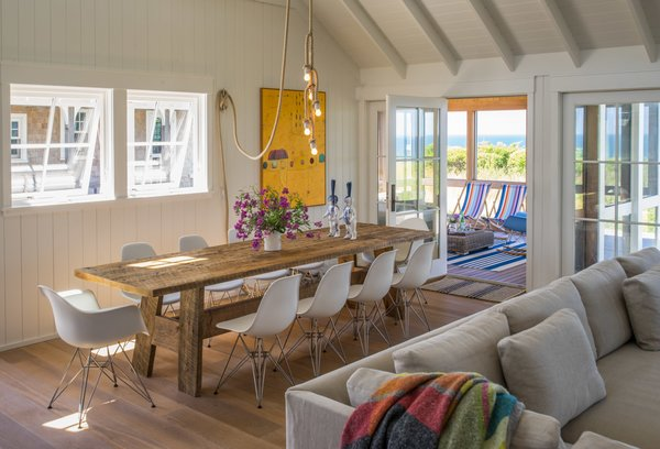 The dining area is furnished with a 10 foot long, rough hewn recycled timber table and contrasting classic Eames chairs. Photo 9 of Corkin House modern home