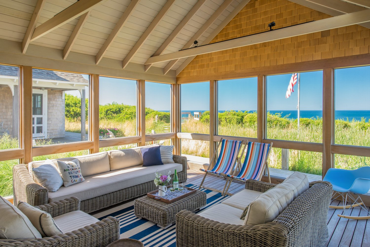 A spacious three-sided screened porch, conveniently located adjacent to the living/dining/kitchen area, is nestled on the edge of a dune overlooking the refreshing waters of Cape Cod Bay.  Corkin House by KRUEGER ASSOCIATES ARCHITECTS
