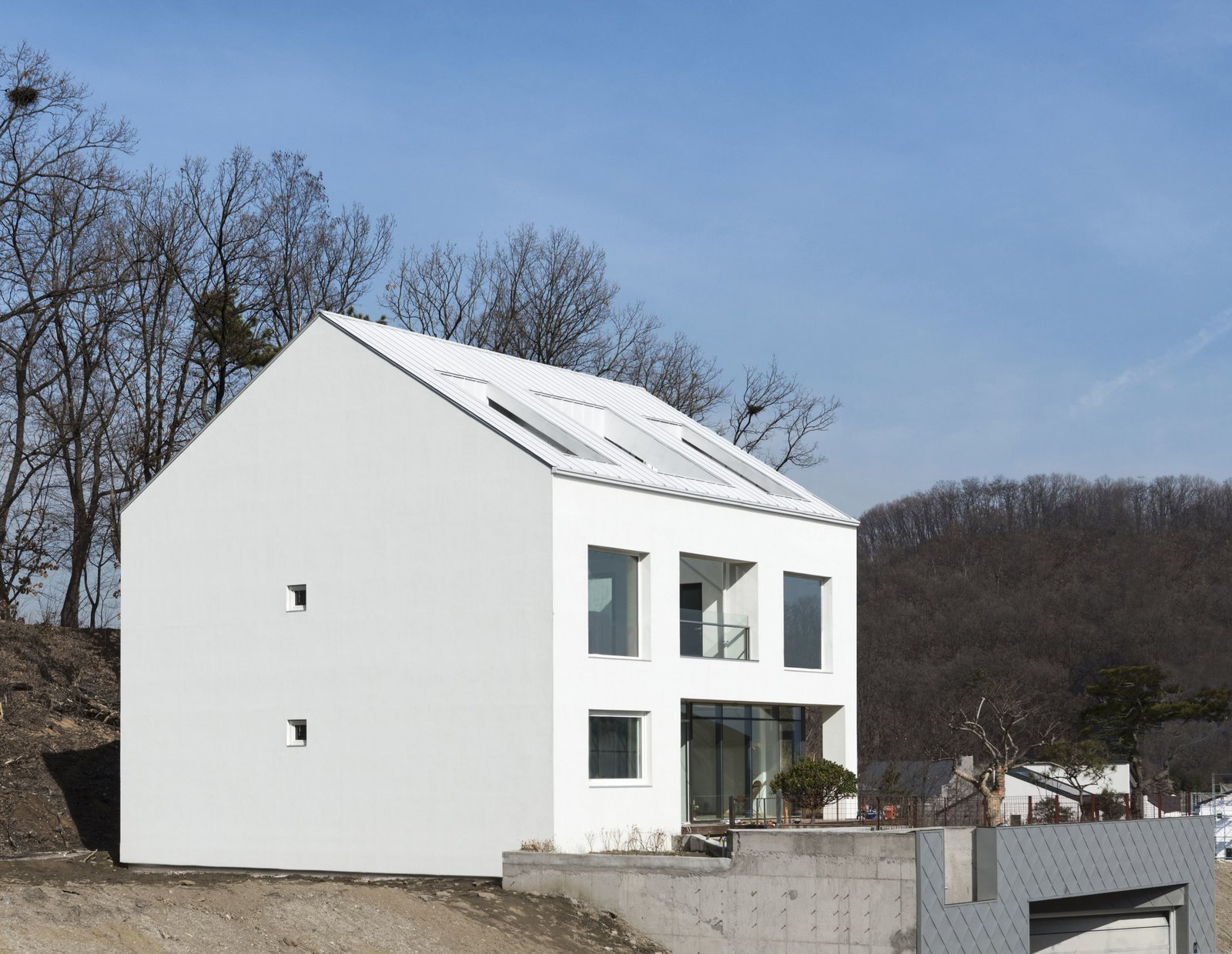 South-East Elevation Tagged: Side Yard, Concrete Patio, Porch, Deck, Outdoor, and Back Yard.  A House by Chang Kyu Lee