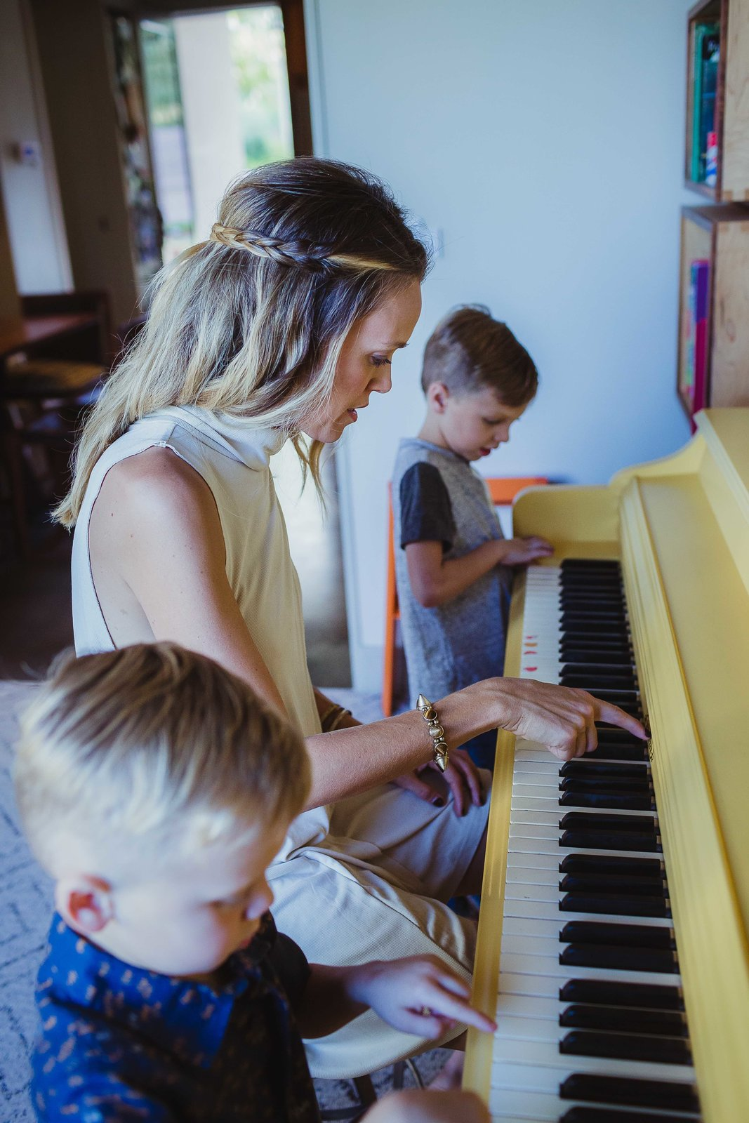 """The piano was Young's wife's when she was growing up and it was originally a very boring, oak brown. """"We wanted it to be the signature feature of the room and painting it yellow is always a fun surprise when you walk in the room. This is the room you can find us in most nights playing board games, playing piano, and drinking wine."""""""