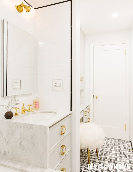 Modern home with bath room, marble counter, drop in sink, ceramic tile floor, drop in tub, open shower, wall lighting, ceiling lighting, subway tile wall, marble wall, and one piece toilet. Bathroom view from window. Photo  of Brooklyn Heights Glam Apartment