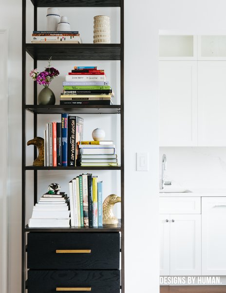 Modern home with kitchen, stone slab backsplashe, white cabinet, engineered quartz counter, dark hardwood floor, ceiling lighting, drop in sink, and dishwasher. Detail of bookcase. Photo 7 of Brooklyn Heights Glam Apartment