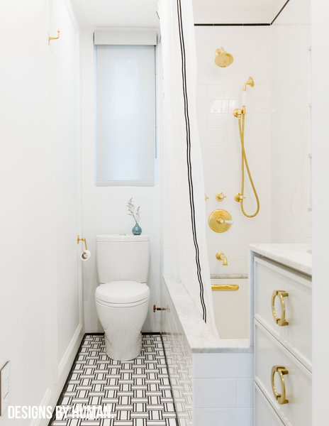 Modern home with bath room, drop in sink, marble counter, drop in tub, marble floor, open shower, wall lighting, ceiling lighting, subway tile wall, marble wall, and two piece toilet. Overall view of bathroom. Photo 4 of Brooklyn Heights Glam Apartment