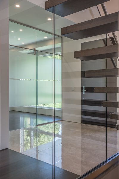 The glass wall allows light and  views under the stairs, making the basement stairs inviting, and allowing for expansive sitelines. Photo 2 of Shadow on White Pallet modern home