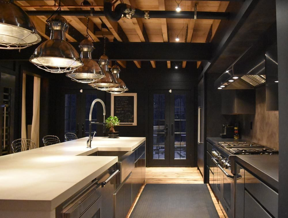Designed to cook.  Galley Kitchen.  Stainless Steel Cabinets inside and out shown on the left, and high gloss gray cabinets with stainless interiors shown on the right.  All cast concrete counter tops.  Vintage nautical lights sourced abroad and originally from somewhere interesting I'm sure...  Thermador Applaiances, wide plank oak flooring, exposed oak and steel frame.  The Lodge by Alpha Genesis