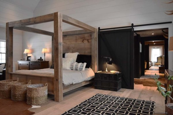 """1,400lb King Bed.  Built in the space from extra timbers not used in the construction of the home.  20"""" wide oak planks make up the head and foot boards.  4' wide sliding doors, 4' wide traffic areas through the home to provide ease of flow, wide plank oak flooring milled my hand onsite, all wood walls and ceilings. Photo 11 of The Lodge modern home"""