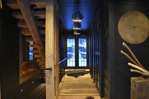 Leading through the house.  Central Foyer is a display of symmetry.  Angus hides.  Axes on display.  Wide plank oak flooring all rough sawn and hand brush sanded. Photo 18 of The Lodge modern home