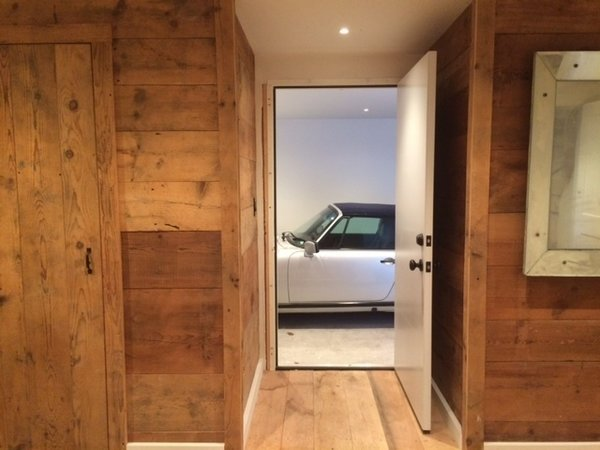 Old Barn plank flooring was reused as wall panels and interior doors.  The surface of the planks were brush sanded and installed naturally without any coating.   Photo 10 of The Red Barn modern home