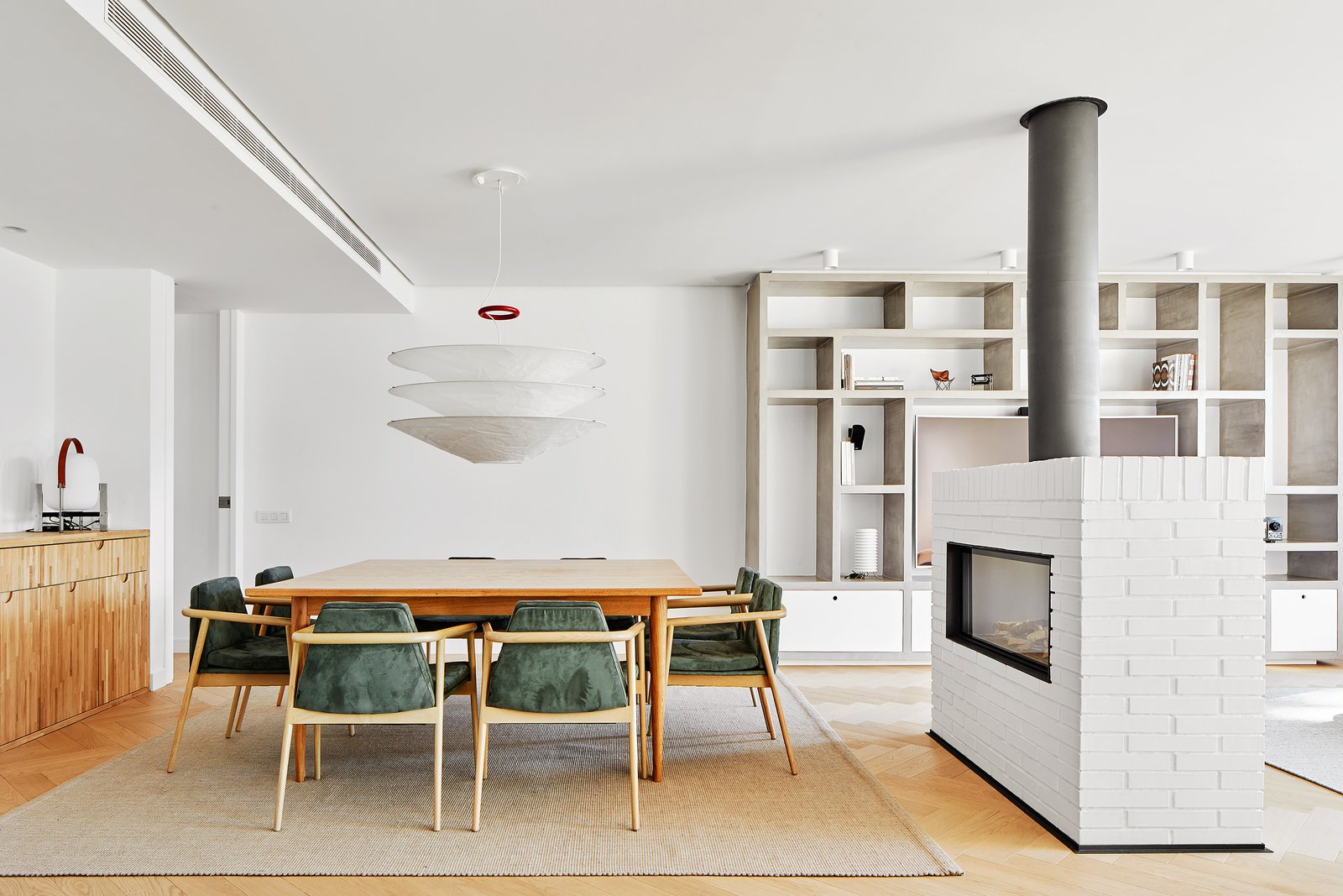 Tagged: Dining Room, Light Hardwood Floor, Two-Sided Fireplace, and Table.  Beautiful Duplex in Barcelona by CONTI, CERT