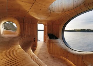 Escape to One of These 10 Otherworldly Outdoor Saunas - Photo 7 of 10 - The space  is lined with CNC-cut wooden panelling that creates a sinuous interior encompassing traditional stepped sauna seating and biomorphic-shaped porthole windows.