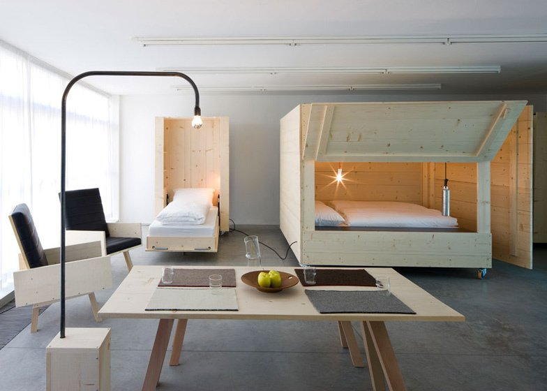 Named Atelierhouse, for contemporary art museum Museion as a temporary home for visiting artists and curators, Harry Thaler Studio employed wooden boxes on wheels fold open to reveal beds inside.    Photo 4 of 11 in 10 Space-Saving Interiors For Multifunctional Living from Space-saving Interiors