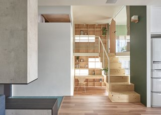 10 Space-Saving Interiors For Multifunctional Living - Photo 7 of 10 -  Behind the blocky staircase, a double-story bookcase covers the entire wall behind with shelves, windows, and even a desk.