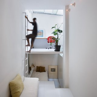 10 Space-Saving Interiors For Multifunctional Living - Photo 8 of 10 - Finished in white, the walls, the floors, and ceiling are contrasted by only splashes of color from sparsely-placed furniture and framed artworks.