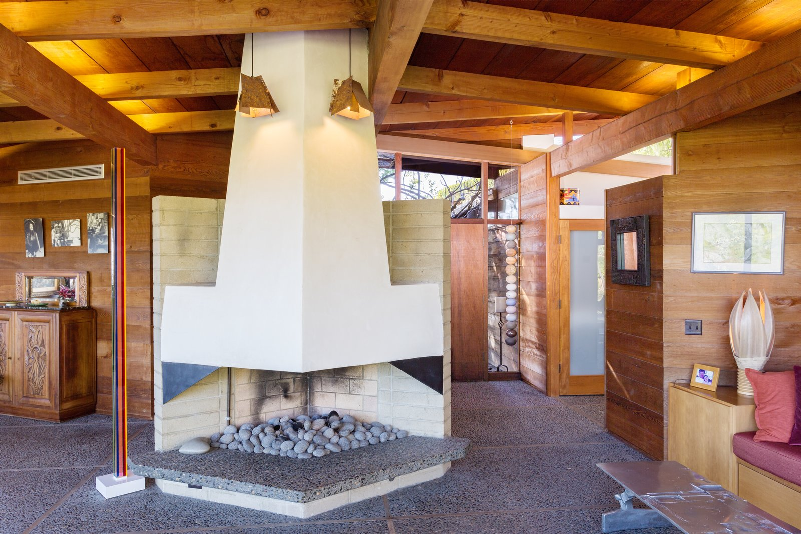 Tagged: Living Room, Wood Burning Fireplace, Concrete Floor, Coffee Tables, and Pendant Lighting.  Photo 7 of 13 in A 1974 Masterpiece Is Put on the Market by a Family Friend of the Late Julius Shulman