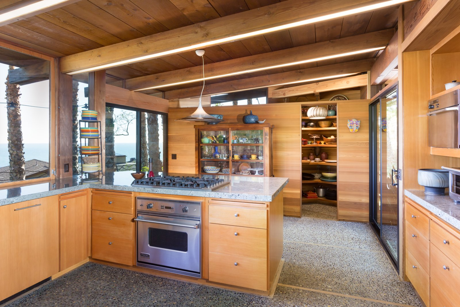 Tagged: Kitchen, Range, Wood Cabinet, Granite Counter, Concrete Floor, and Pendant Lighting.  Photo 11 of 13 in A 1974 Masterpiece Is Put on the Market by a Family Friend of the Late Julius Shulman