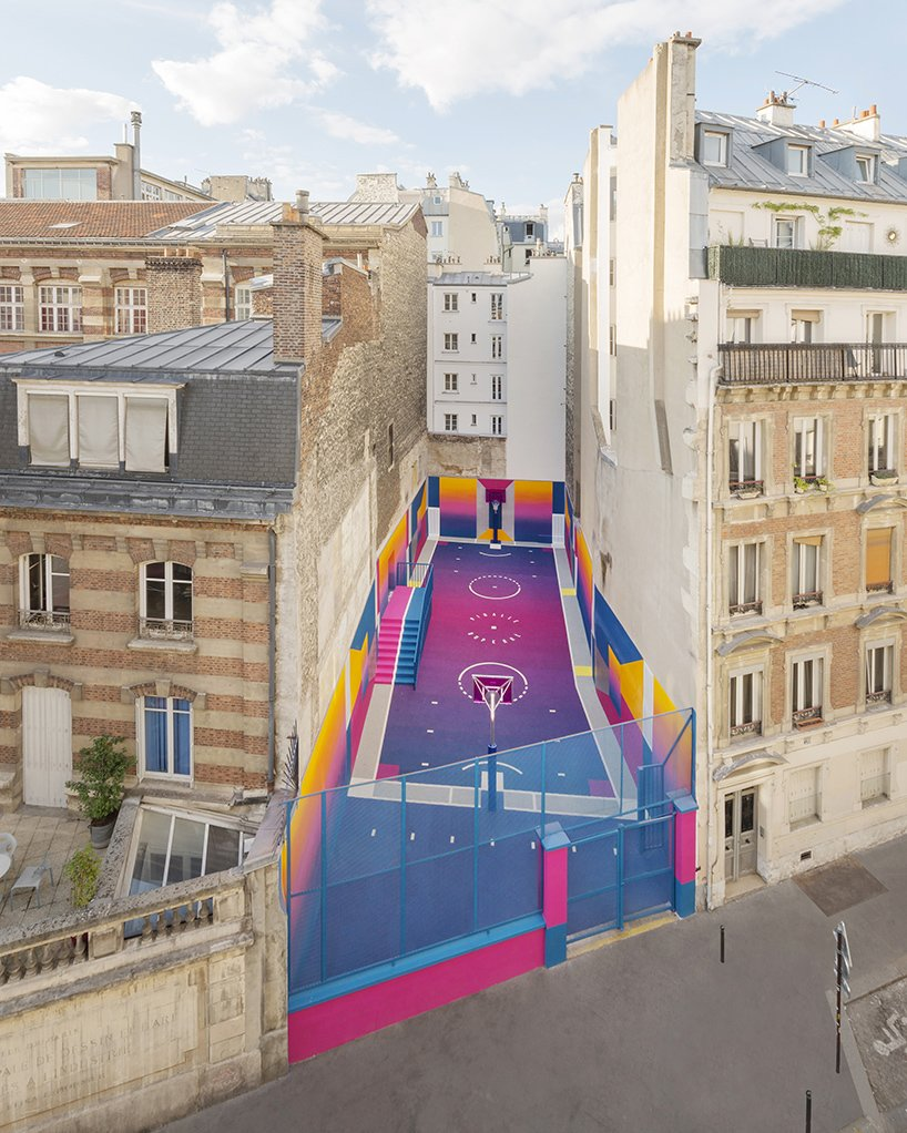Sandwiched in-between a pair of brick apartment buildings in Paris lies a technicolor basketball court.  Basketball fan and founder of the French fashion brand Pigalle, Stéphane Ashpool collaborated with Parisian creative agency Ill-Studio and Nike to make over the site. The basketball court's walls and floor encircle players in saturated and smooth shades, where shots can be made off of a bright pink backboard. The overall effect is set with a vibrant gradient aesthetic featuring a color palette of high-contrast grape, deep yellows, and bold blues. Tagged: Outdoor, Large Patio, Porch, Deck, and Concrete Patio, Porch, Deck.  Best Photos from A Technicolor Basketball Court in Paris