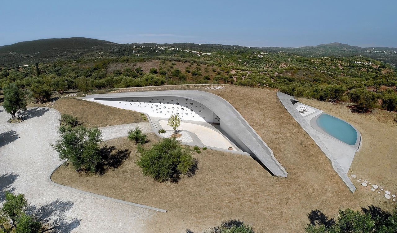 Tagged: Outdoor, Rooftop, Grass, Trees, Shrubs, Hardscapes, and Large Pool. This Y-Shaped Greek Villa Looks Like a Flying Saucer That's Embedded Into the Hills - Photo 2 of 9