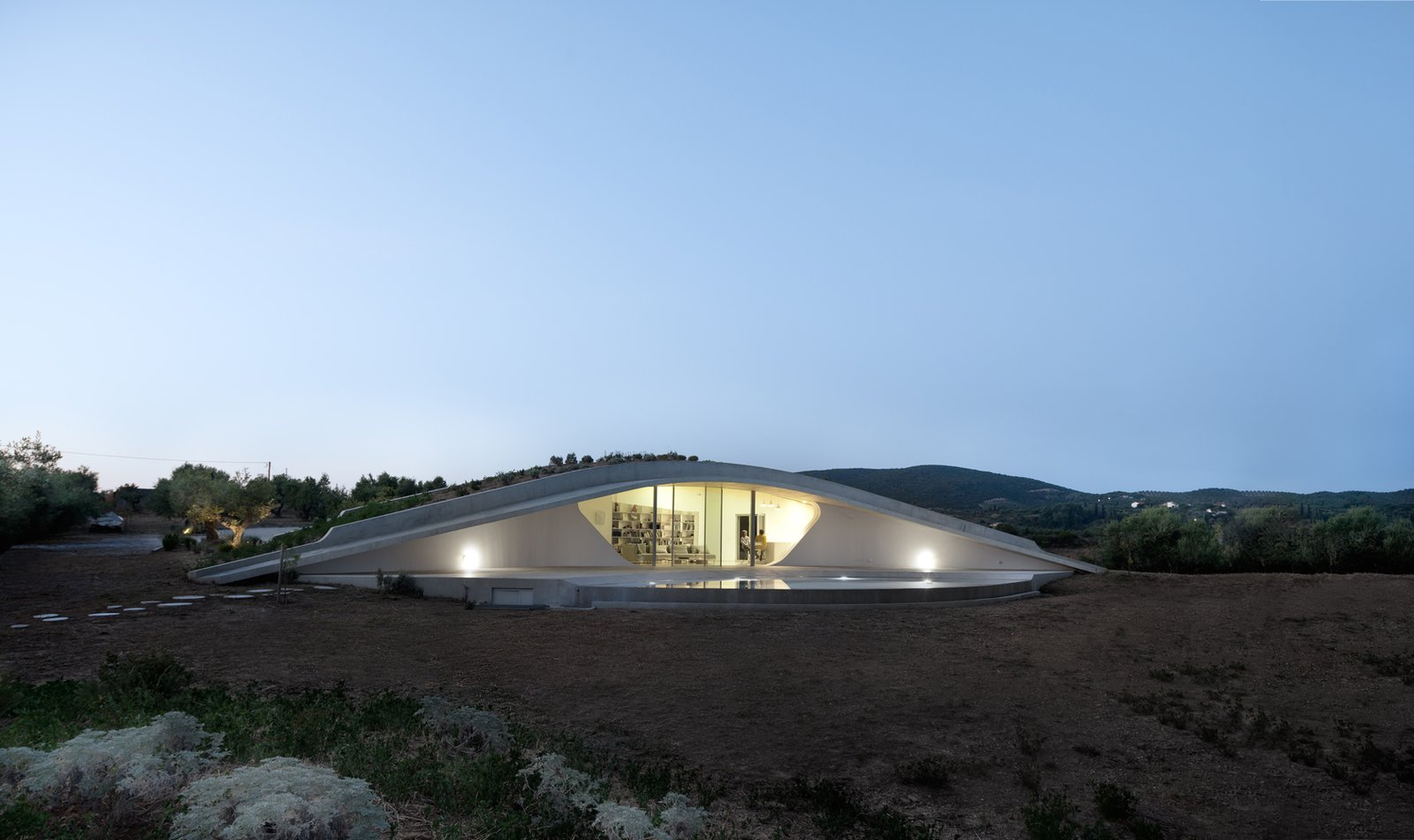Tagged: Outdoor, Trees, Back Yard, Shrubs, Hardscapes, Concrete Patio, Porch, Deck, and Large Pools, Tubs, Shower.  Photo 9 of 9 in This Y-Shaped Greek Villa Looks Like a Flying Saucer That's Embedded Into the Hills