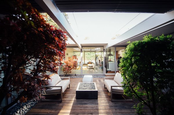 Modern home with living room, coffee tables, stools, sofa, and light hardwood floor. Photo 7 of Renovated Sunnyvale Eichler