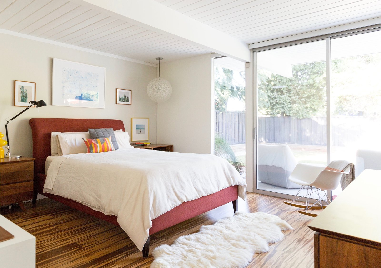 Tagged: Bedroom, Bed, Night Stands, Pendant Lighting, Dresser, Rockers, Medium Hardwood Floor, and Table Lighting.  Photo 10 of 11 in An Interior Designer Launches Her Career by Renovating Her Family's Midcentury Eichler