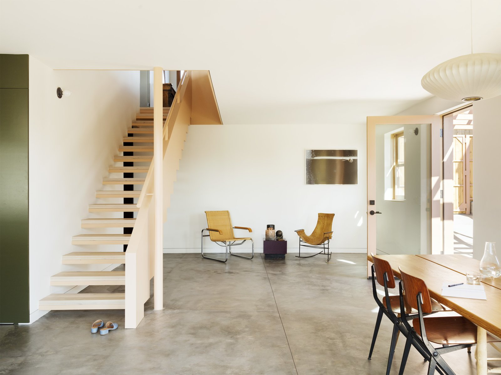 Tagged: Chair, Concrete Floor, Wood Tread, Wood Railing, Living Room, End Tables, Pendant Lighting, and Table Lighting.  Photo 4 of 14 in Grids and Colors Inspire the Renovation of a Graphic Designer's Pink L.A. Bungalow