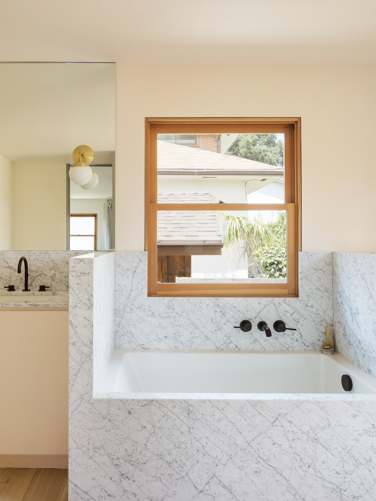 Tagged: Bath Room, Marble Counter, Soaking Tub, Light Hardwood Floor, Undermount Sink, and Wall Lighting.  Photo 11 of 14 in Grids and Colors Inspire the Renovation of a Graphic Designer's Pink L.A. Bungalow