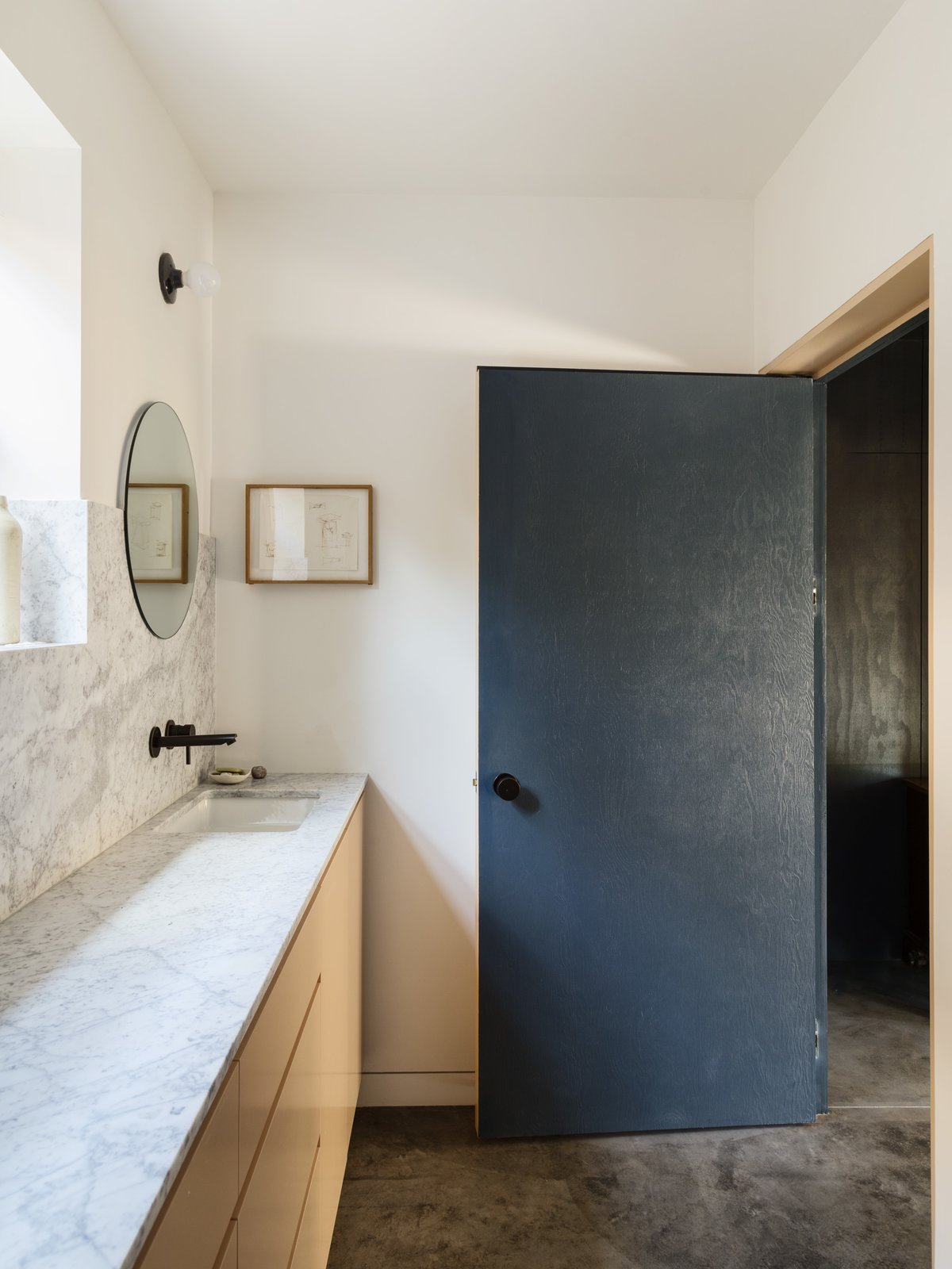 Tagged: Bath Room, Marble Counter, Concrete Floor, Undermount Sink, and Wall Lighting.  Photo 10 of 14 in Grids and Colors Inspire the Renovation of a Graphic Designer's Pink L.A. Bungalow
