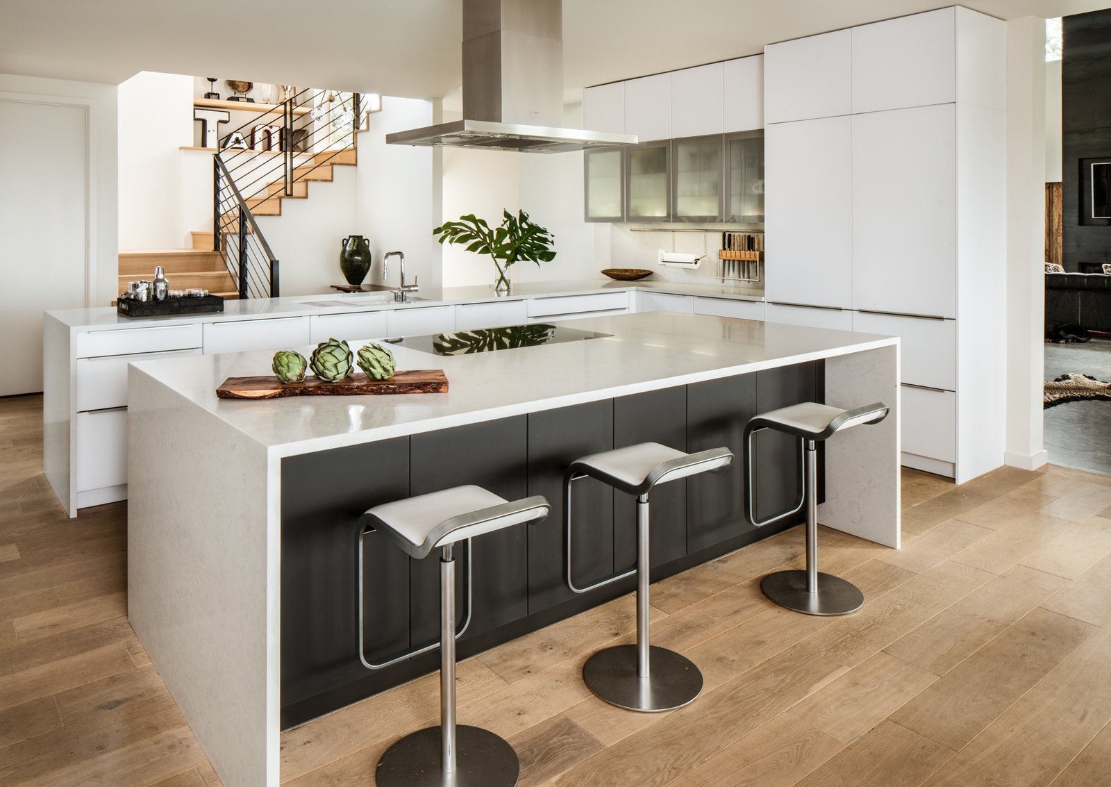 Modern home with Kitchen, Engineered Quartz Counter, White Cabinet, Light Hardwood Floor, Range Hood, and Cooktops. Kitchen Photo 10 of River Garden Trail Residence