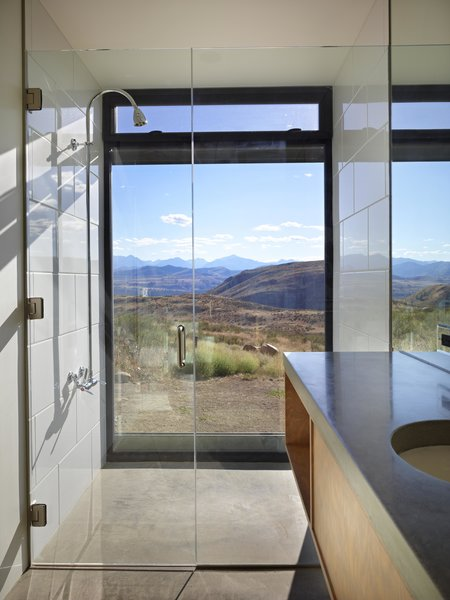 Modern home with bath room, undermount sink, concrete counter, ceramic tile wall, and full shower. Studhorse | Olson Kundig Photo 15 of Studhorse
