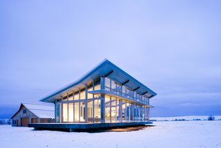 10 Modern Glass Homes - Photo 7 of 10 - Surrounded by wheat fields on a high-altitude plateau stands a small glass house and a solid, traditional barn. The owners, inspired by Philip Johnson's Glass House, wanted a refuge that opens up to the prairie and mountains.