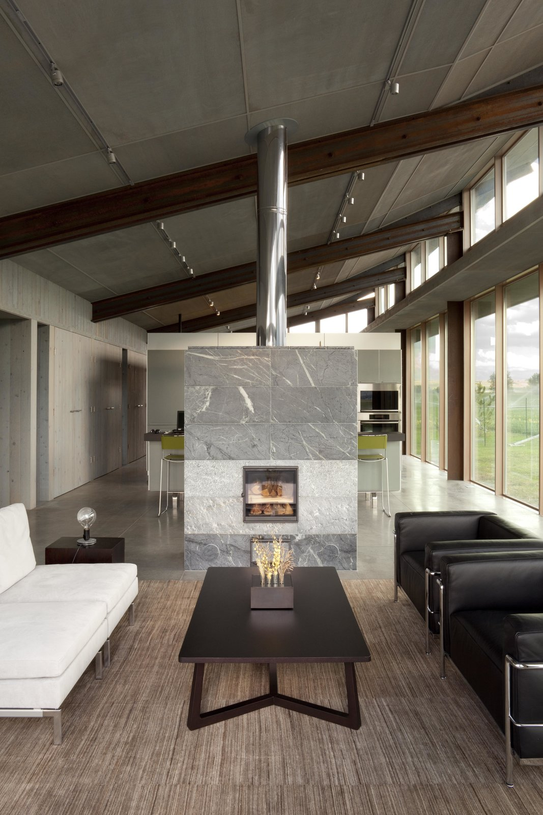 Glass Farmhouse | Olson Kundig Tagged: Living Room, Standard Layout Fireplace, Gas Burning Fireplace, Concrete Floor, Sofa, Coffee Tables, Track Lighting, and Chair.  Glass Farmhouse by Olson Kundig