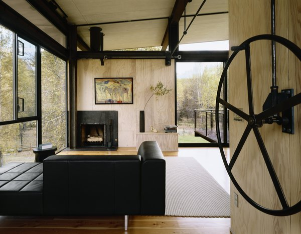 Modern home with living room, standard layout fireplace, sofa, and medium hardwood floor. Delta Shelter | Olson Kundig Photo 5 of Delta Shelter