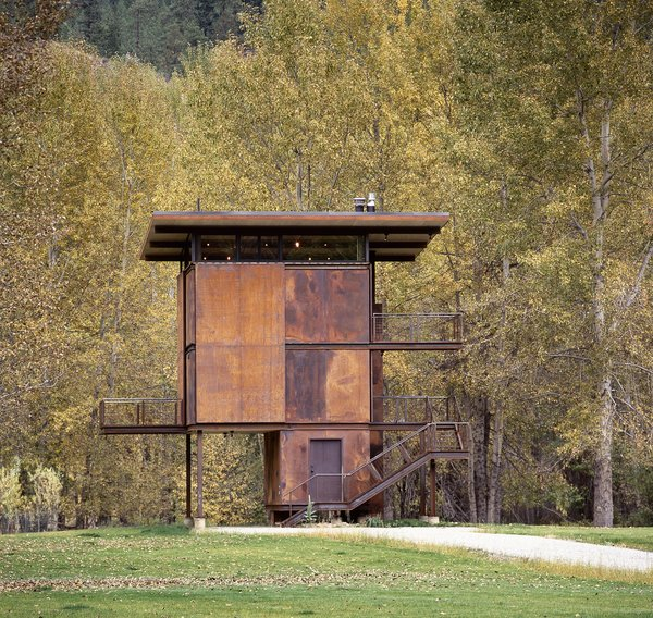 Modern home with outdoor, front yard, small patio, porch, deck, metal patio, porch, deck, woodland, trees, and grass. Delta Shelter | Olson Kundig Photo  of Delta Shelter