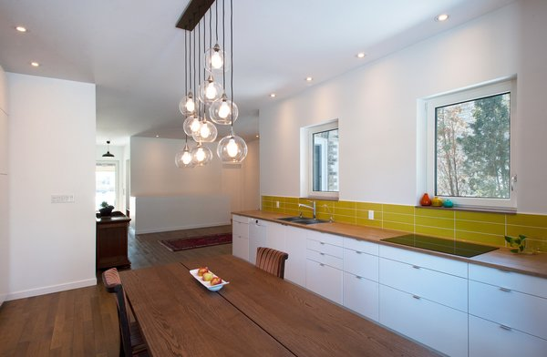 Modern home with wood counter, medium hardwood floor, subway tile backsplashe, ceiling lighting, pendant lighting, accent lighting, drop in sink, cooktops, dining room, and table. Guelph Deep Energy Retrofit - Kitchen and Dining Room Photo 8 of Guelph Deep Energy Retrofit