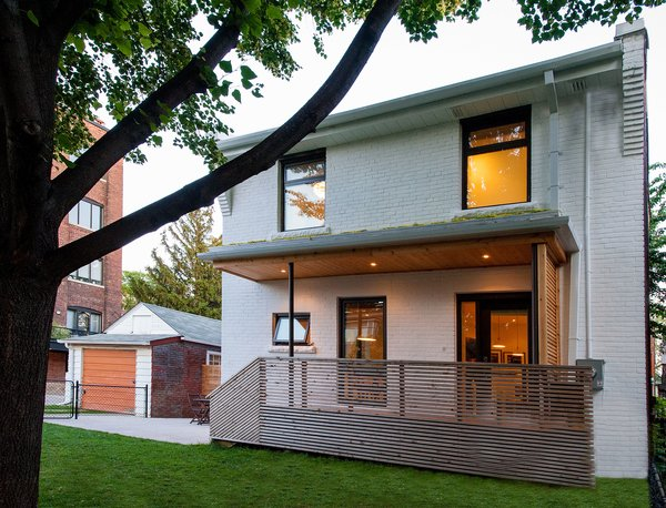 Modern home with outdoor, trees, grass, front yard, wood patio, porch, deck, wood fence, horizontal fence, and small patio, porch, deck. Our House - Exterior Photo  of Our House