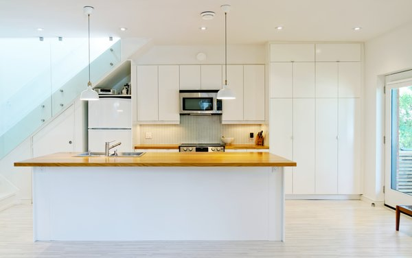 Modern home with light hardwood floor, ceiling lighting, wood counter, white cabinet, pendant lighting, drop in sink, microwave, dishwasher, staircase, and glass railing. Our House - Kitchen Photo 12 of Our House